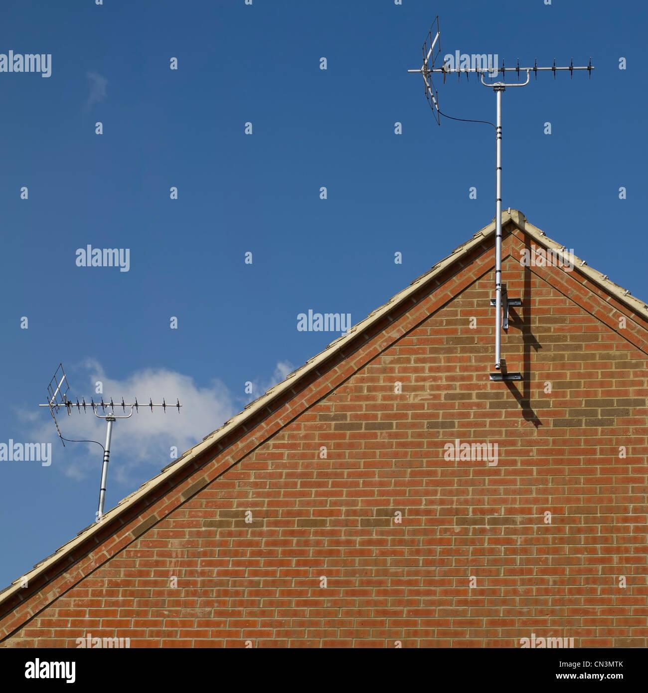 TV Antenne auf einem Hausdach, umrahmt von einem blauen Himmel ...