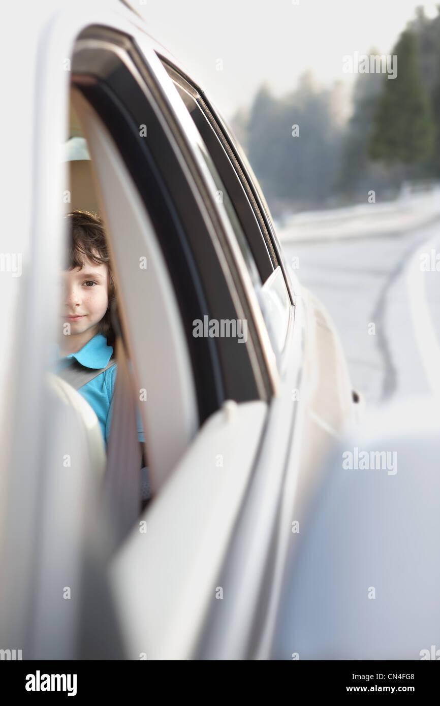 Junge sitzt auf dem Rücksitz eines Autos Stockbild