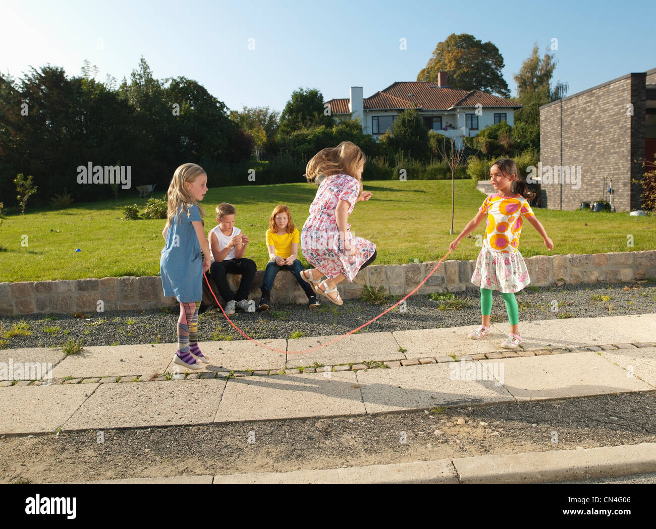Mädchen auf Bürgersteig überspringen Stockbild