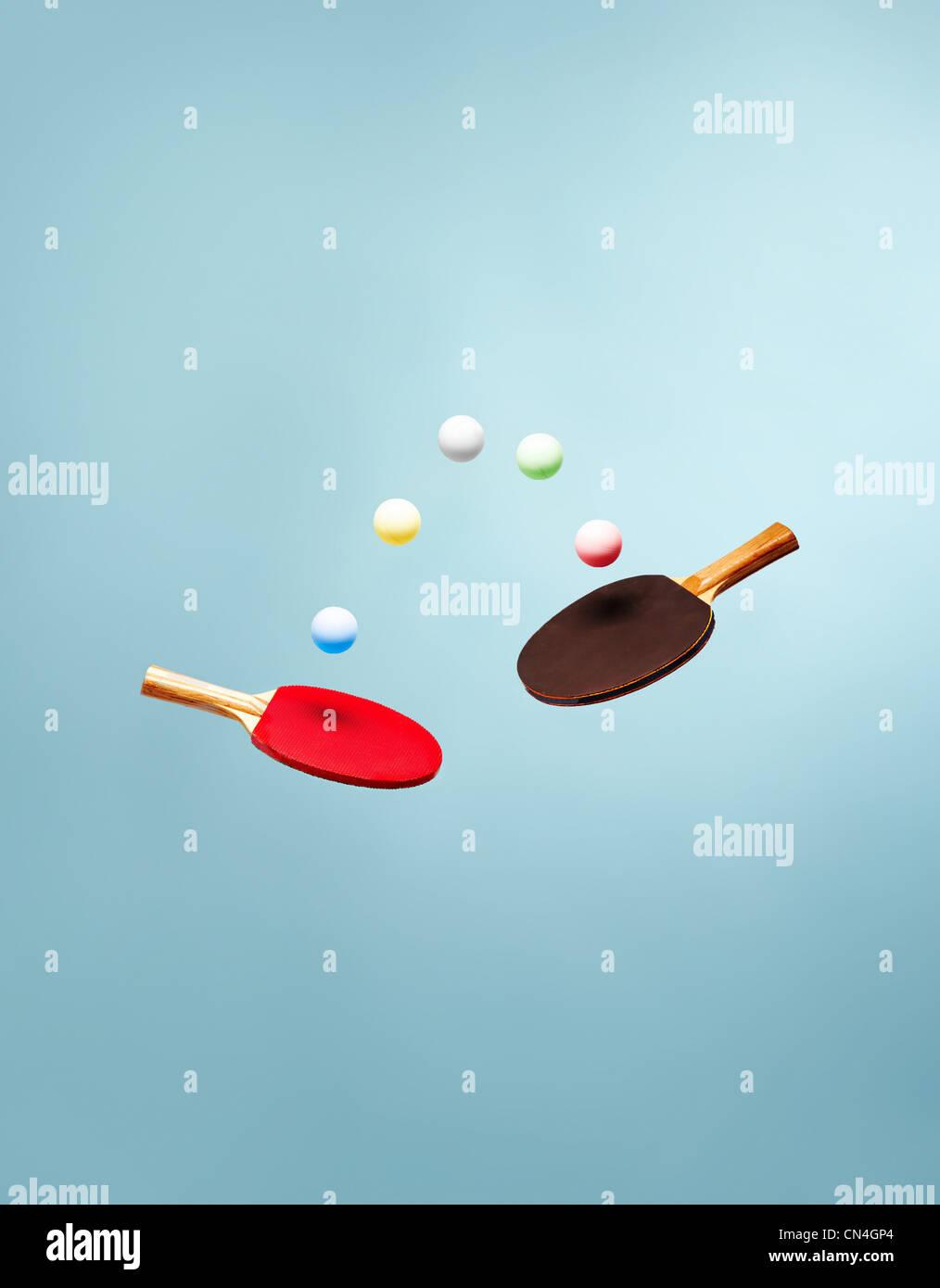 Tischtennisschläger und Kugeln in der Luft schweben Stockbild