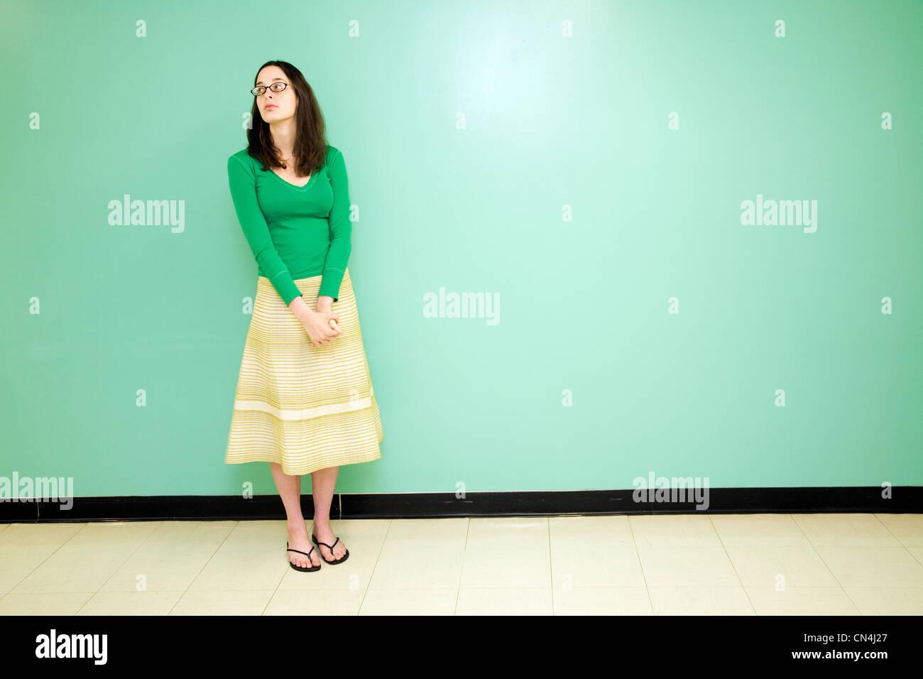 Junge Frau gegen eine grüne Wand Stockbild