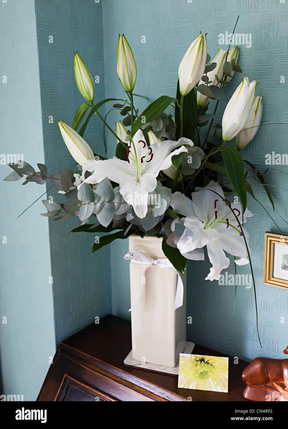 Weiße Lilien in Vase als Beileid nach Trauerfall, Wales, UK Stockbild
