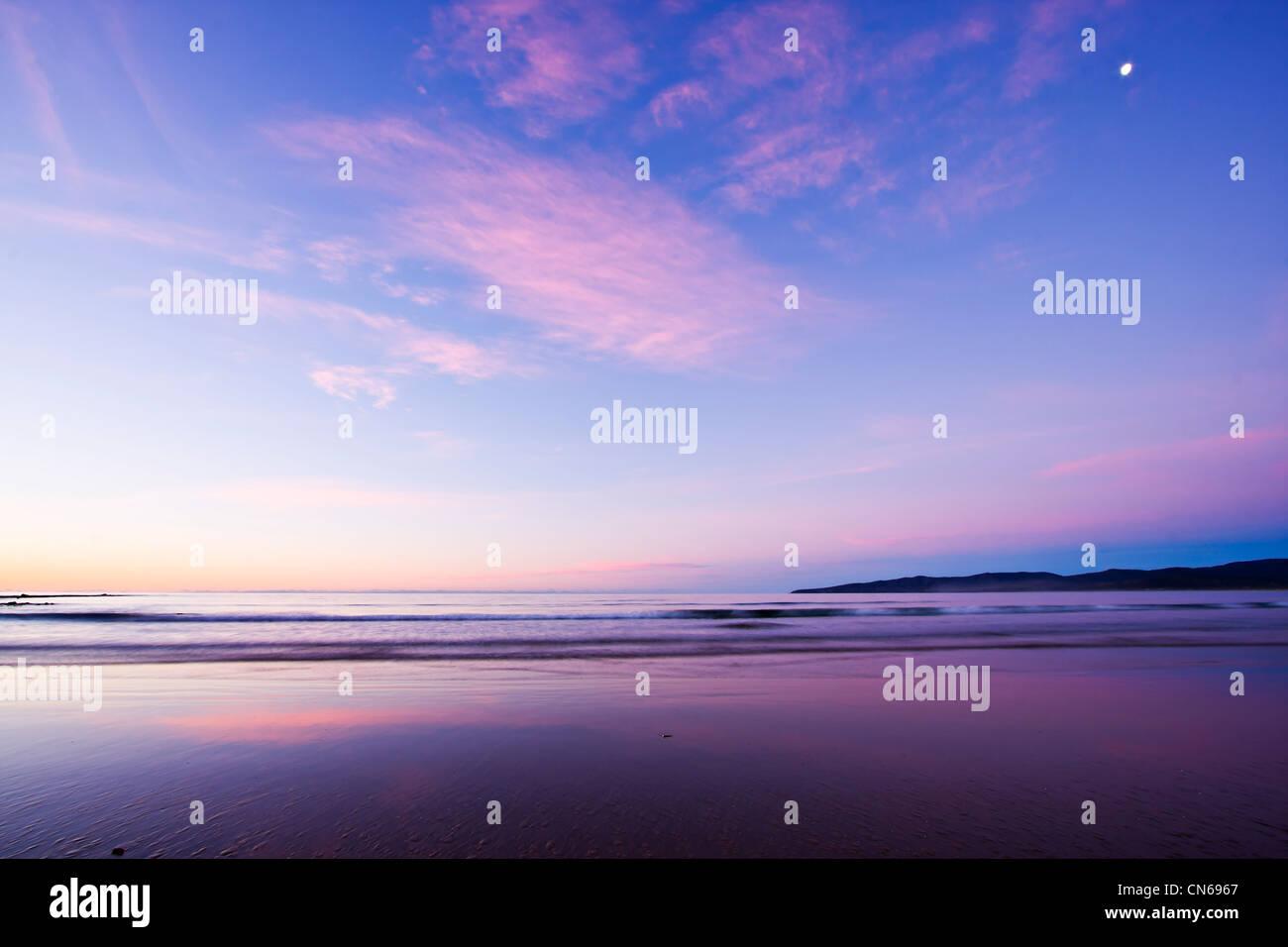 Einbruch der Dunkelheit Farben und Reflexionen am Strand nach Sonnenuntergang Stockfoto