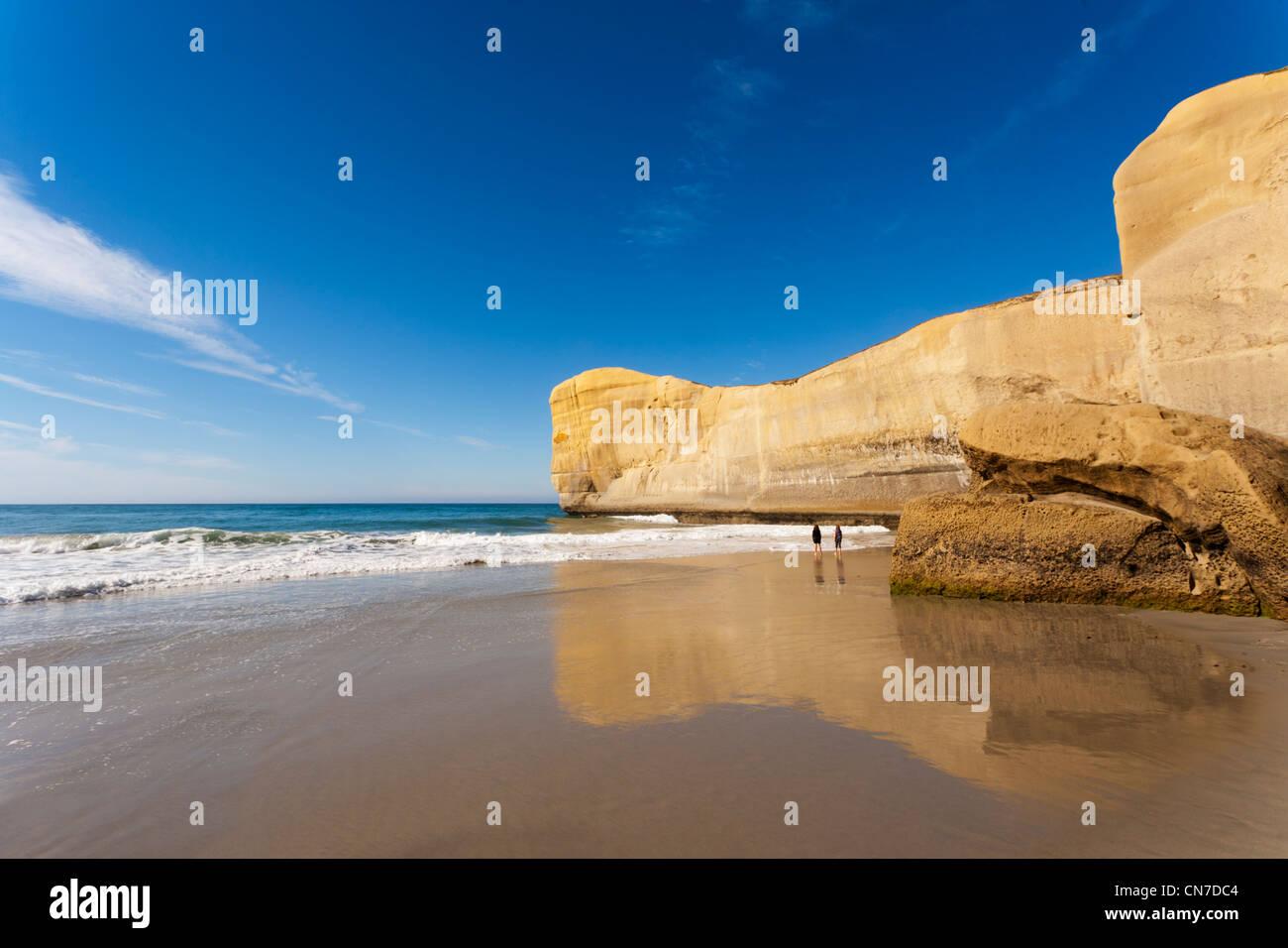 Tunnel Beach, Dunedin, Otago, zwei Mädchen am Strand stehen. Stockfoto