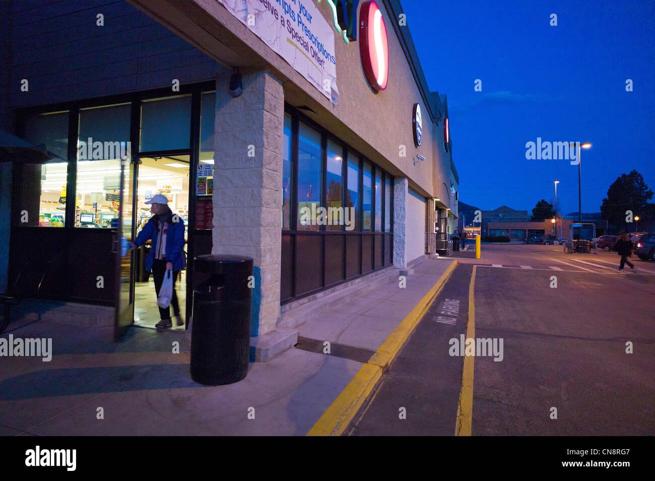 Weibliche Käufer verlassen einen Safeway-Supermarkt in der Abenddämmerung, Salida, Colorado, USA Stockbild