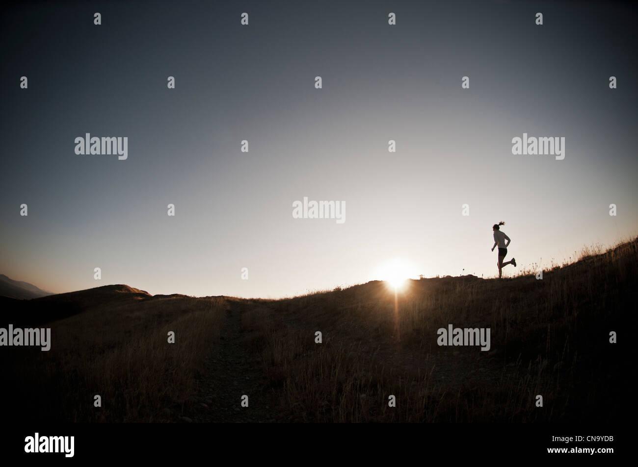 Frau läuft auf Feldweg Stockbild