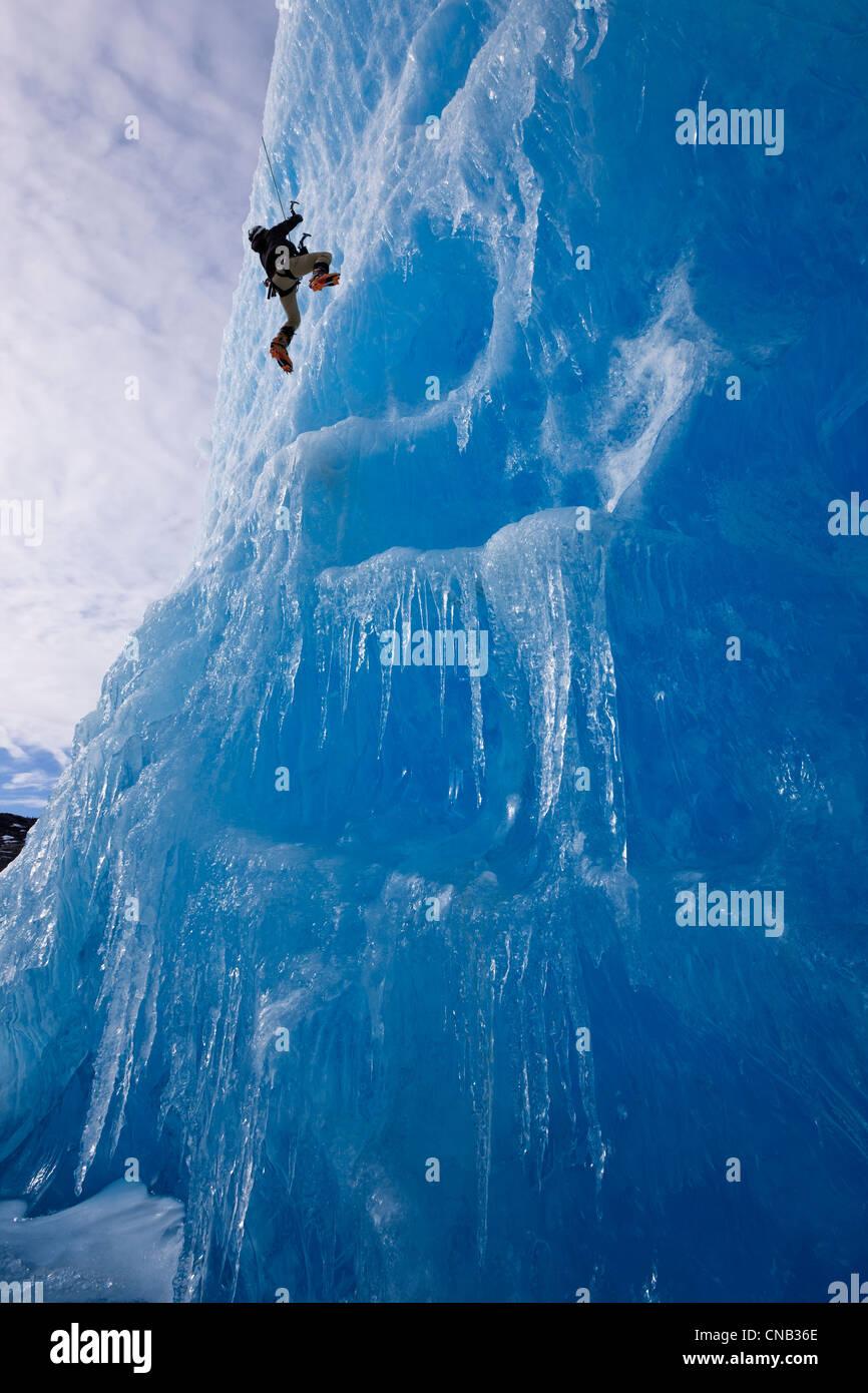 Ein Eiskletterer steigt das Gesicht eines großen Eisbergs in Mendenhall Lake, Juneau, südöstlichen Stockbild
