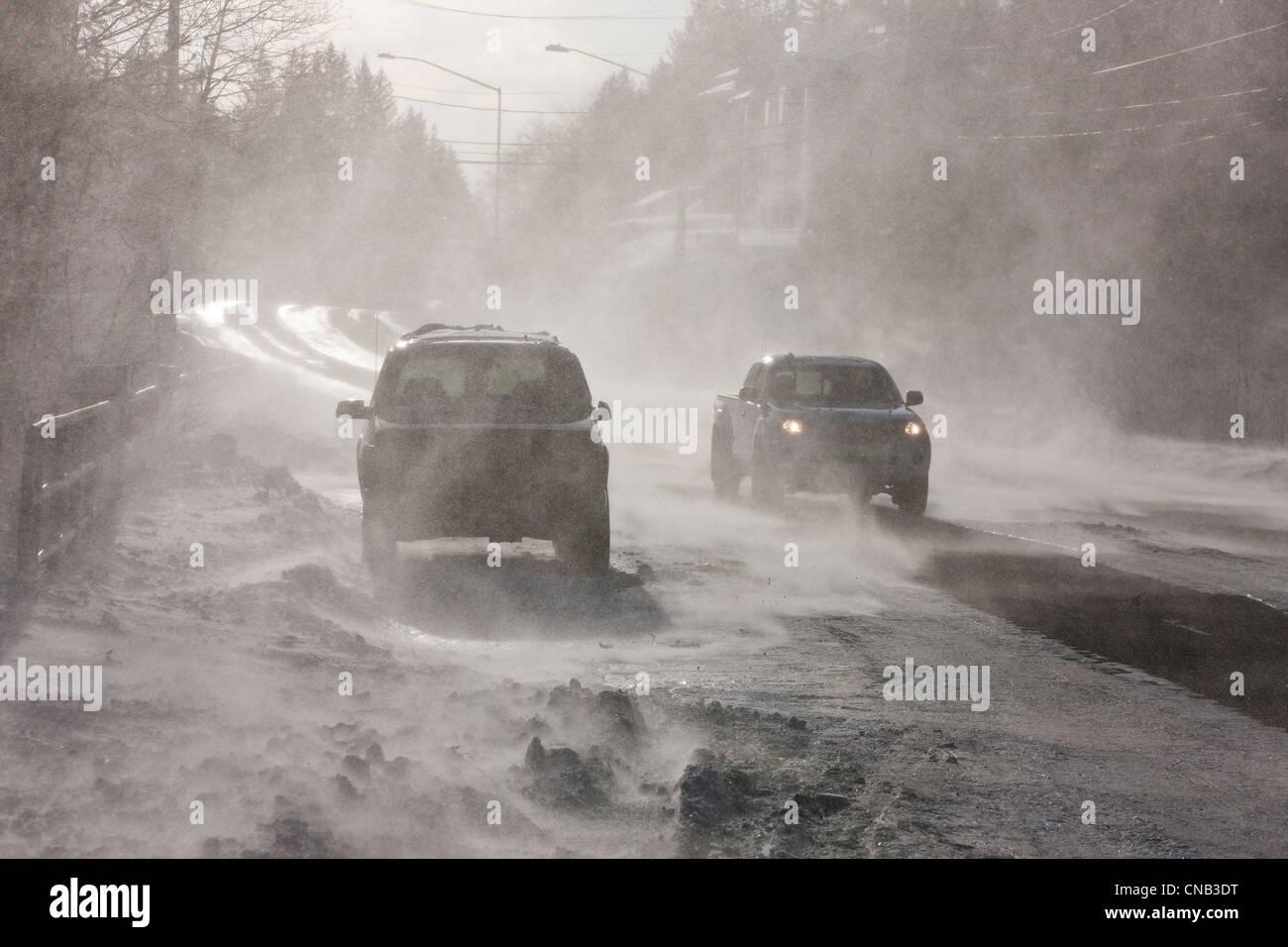 Fahrzeuge fahren auf Douglas Fahrbahn von 70 mph weht Wind und Schnee, Juneau, südöstlichen Alaska Winter Stockbild