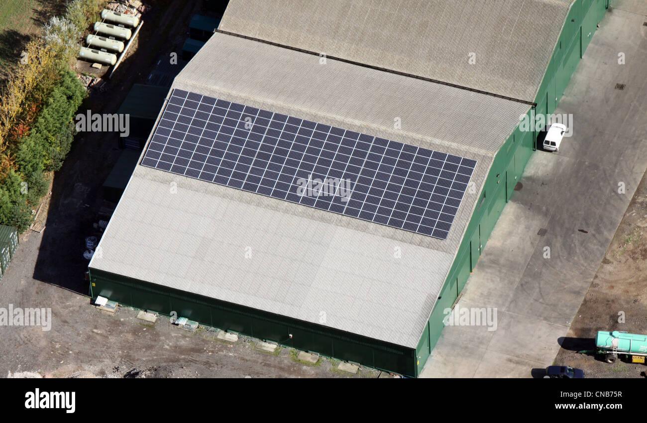 Luftaufnahme von Sonnenkollektoren auf ein landwirtschaftliches Gebäude Stockbild