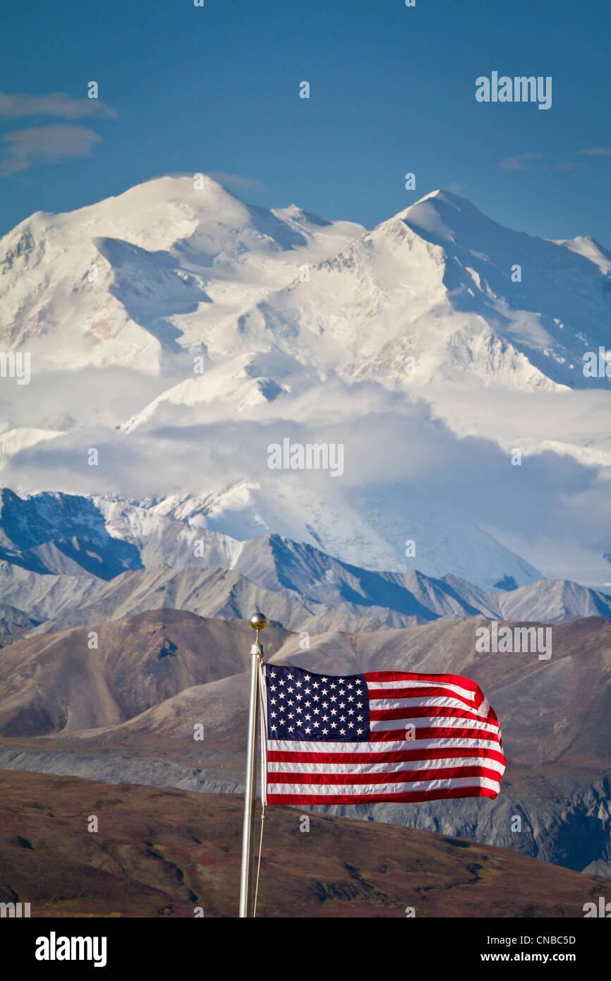 Eine amerikanische Flagge fliegt im Wind im Eielson Visitor Center mit Mt. Mckinley im Hintergrund, Denali-Nationalpark, Stockbild