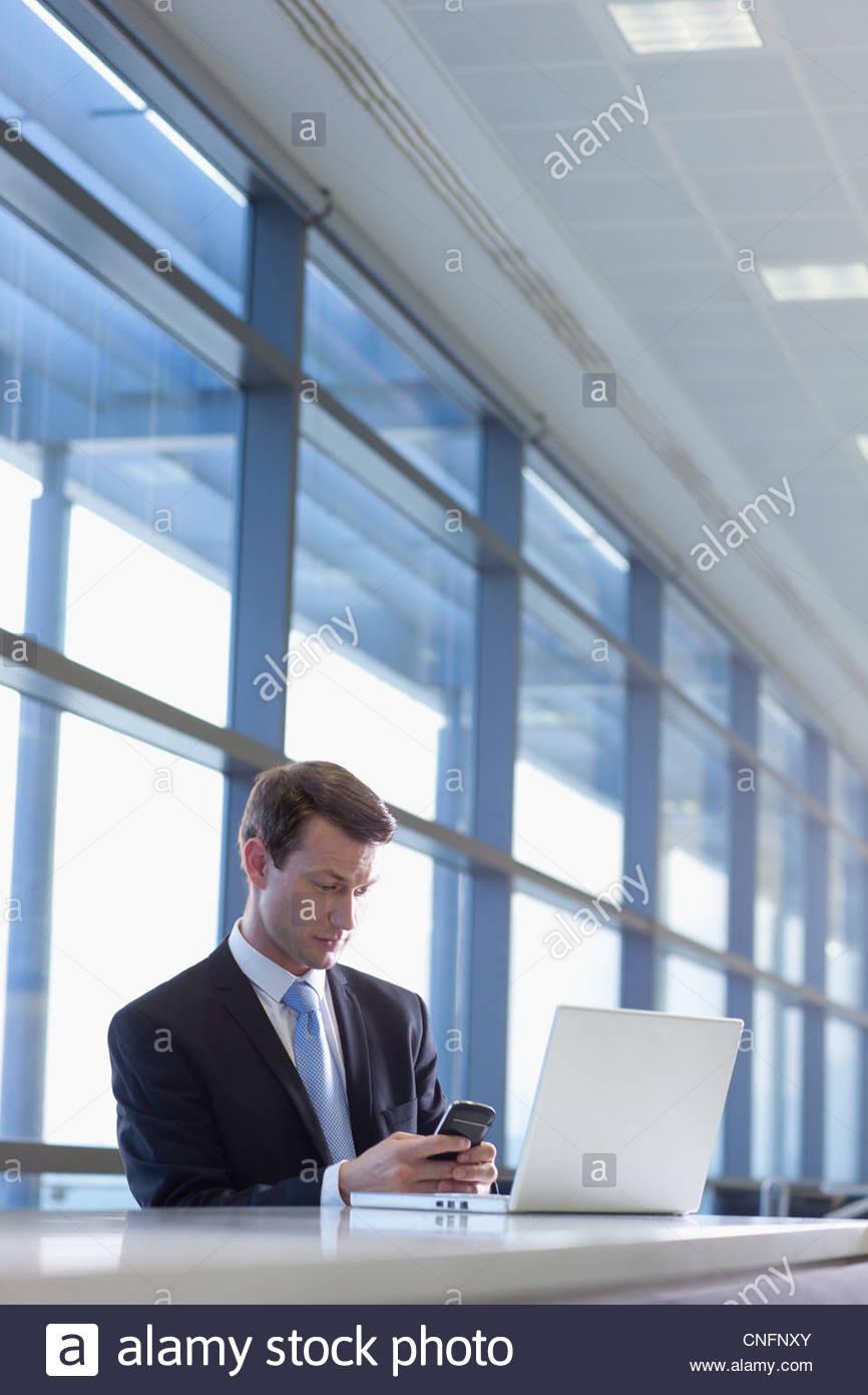 Geschäftsmann mit Laptop und SMS auf Handy im Büro Stockbild