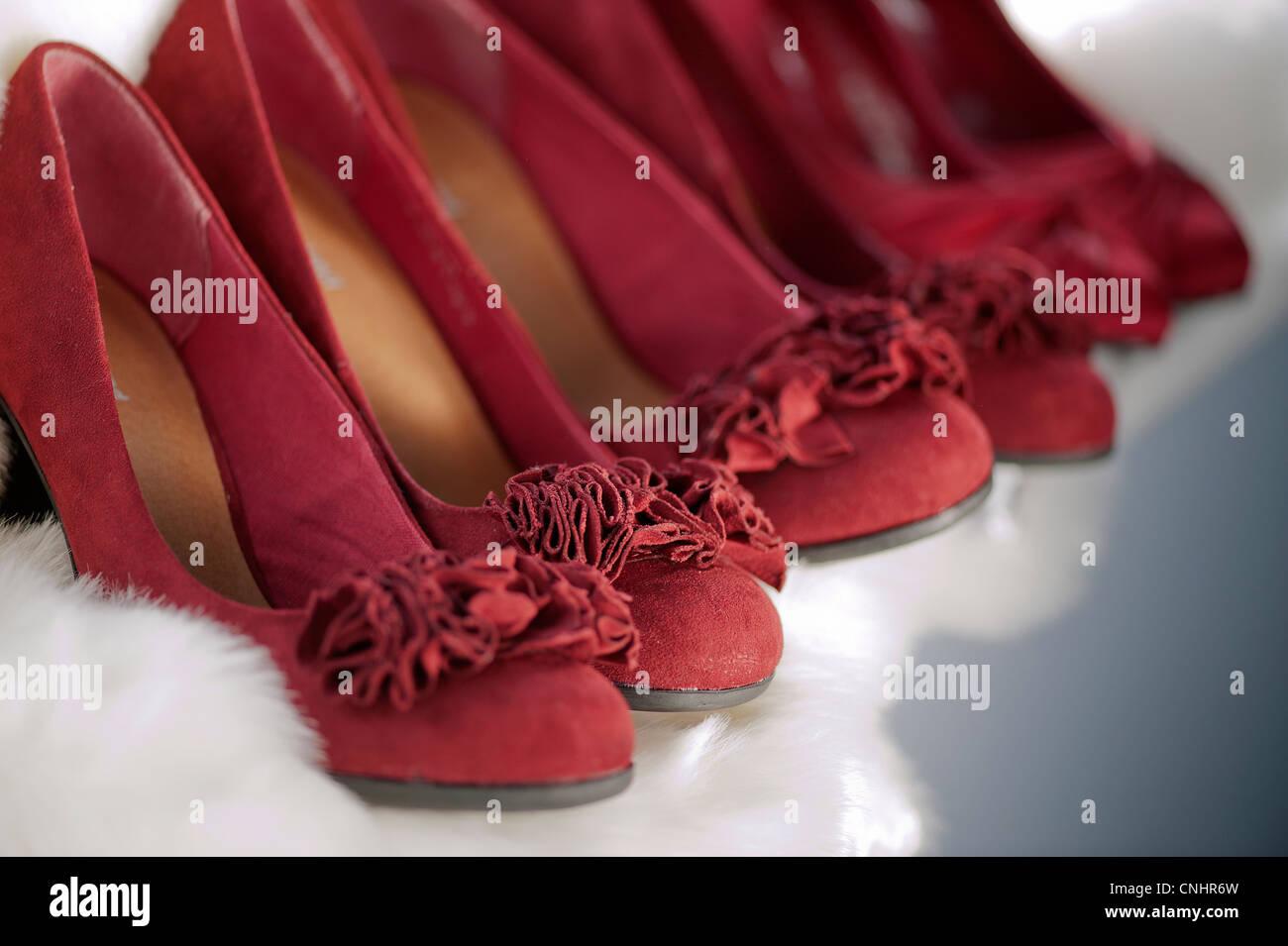 Linie der roten Wildleder Brautjungfer Womens Stöckelschuhe auf einem weißen Fell-Hintergrund Stockbild