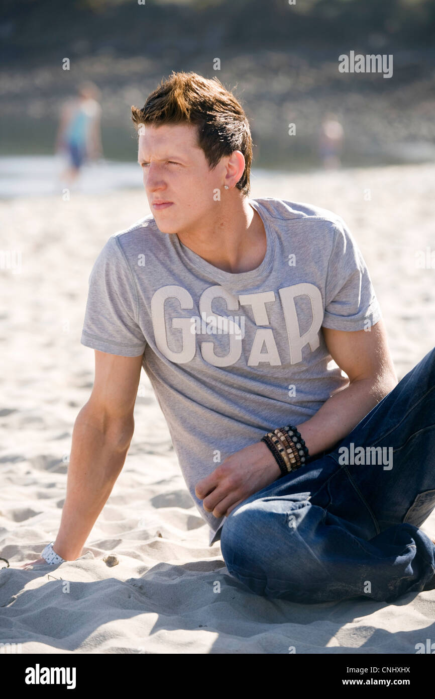 Mann sitzt am Strand mit Blick weg von der Kamera. Stockbild