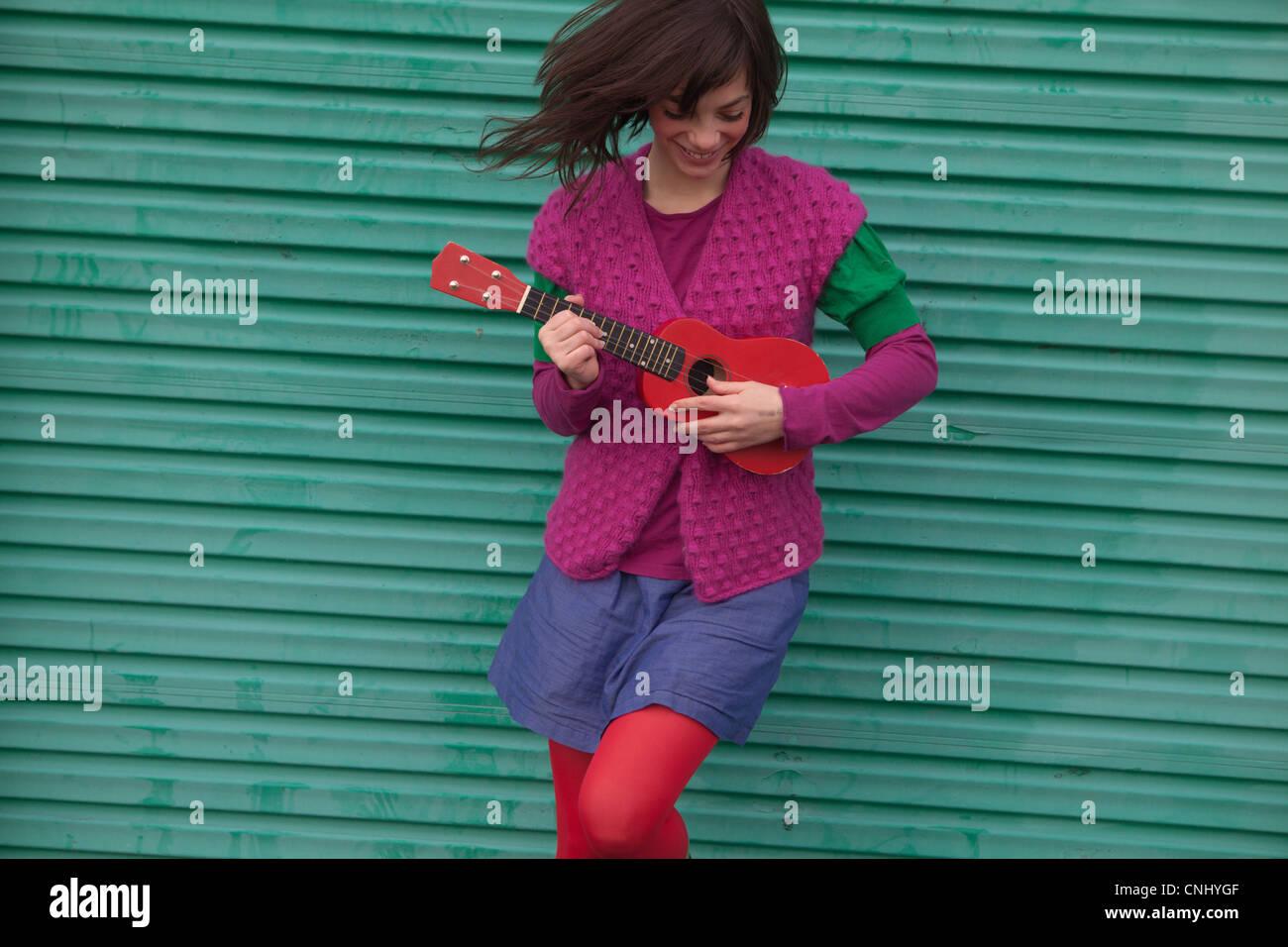 Junge Frau spielt ukulele Stockbild
