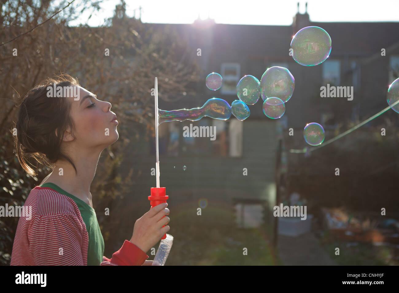 Junge Frau bläst Seifenblasen im freien Stockbild