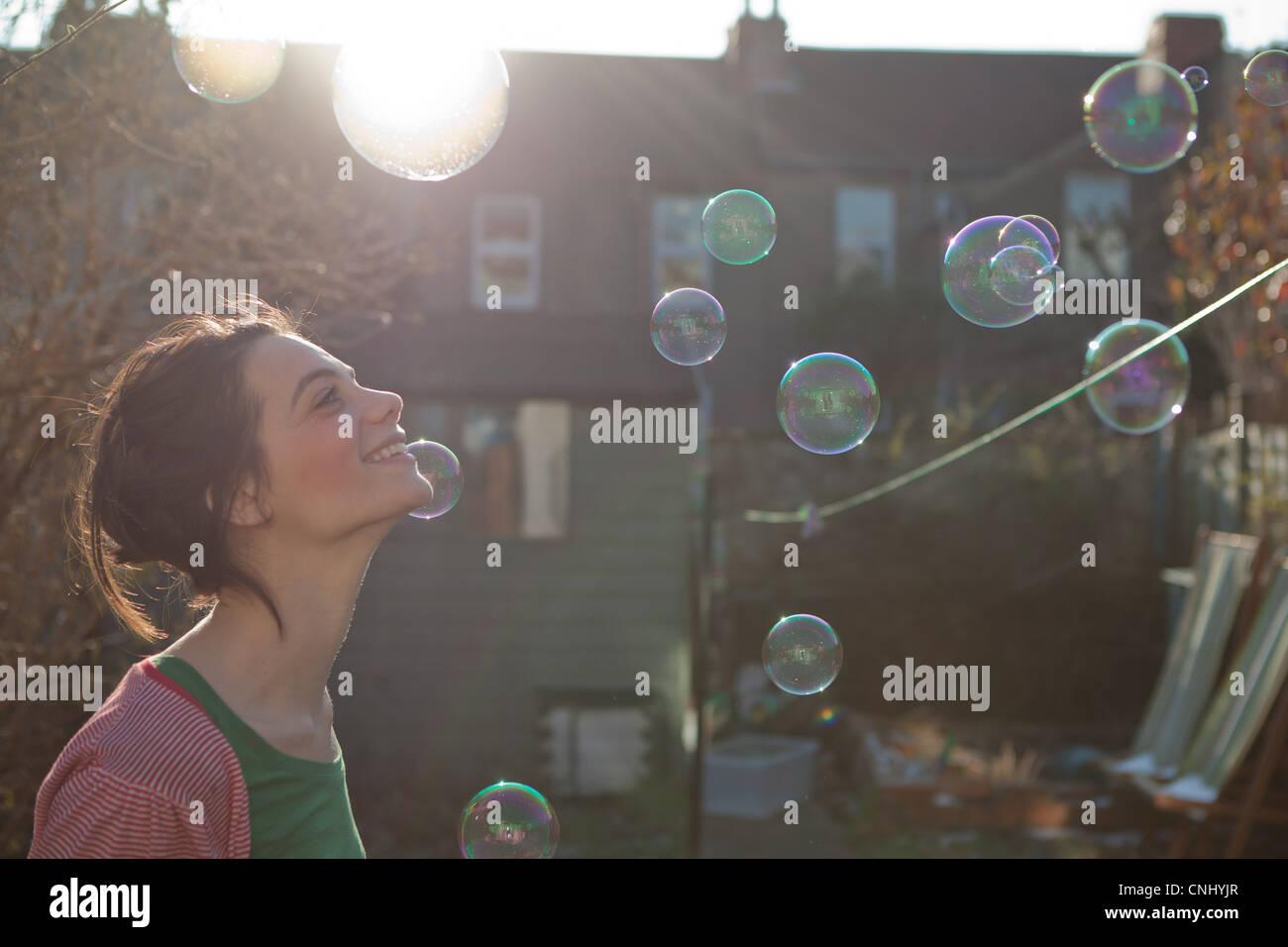 Junge Frau im Freien mit Luftblasen in der Luft schweben Stockbild