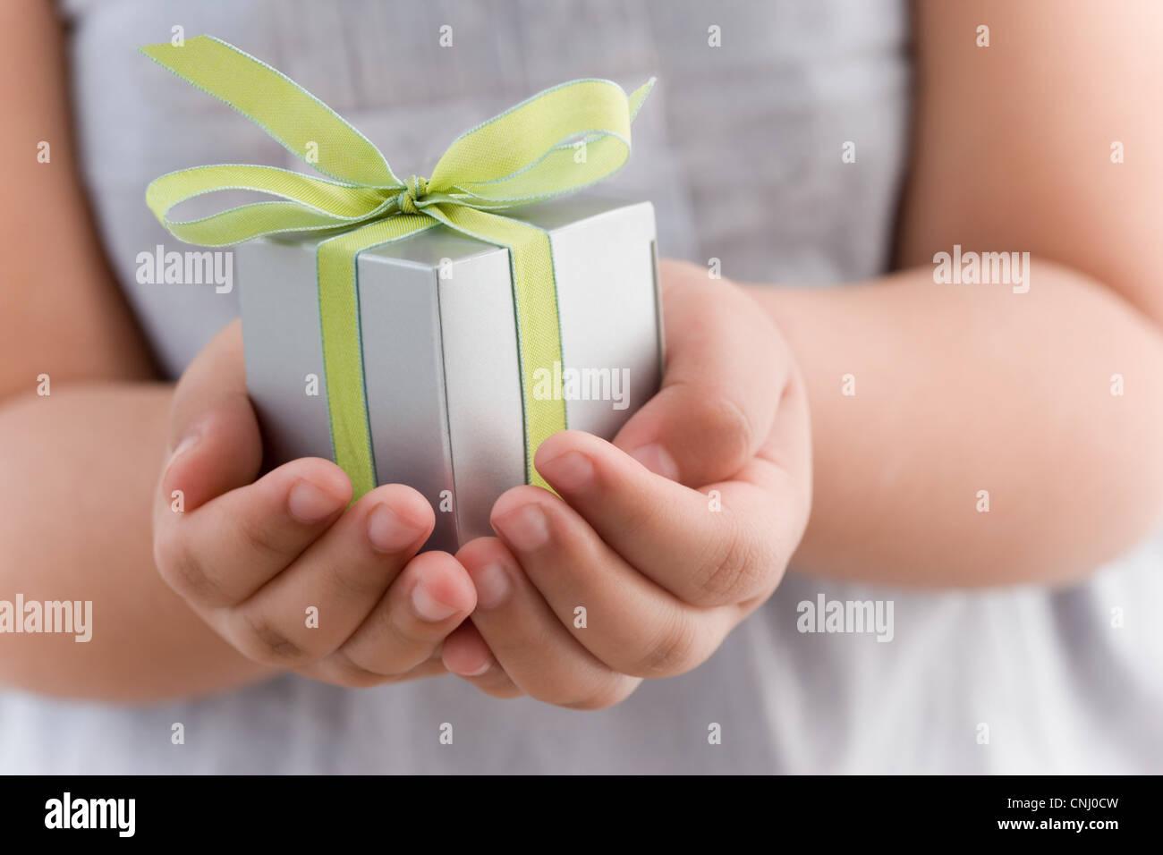 Mädchen hält ein kleines Geschenk Stockbild
