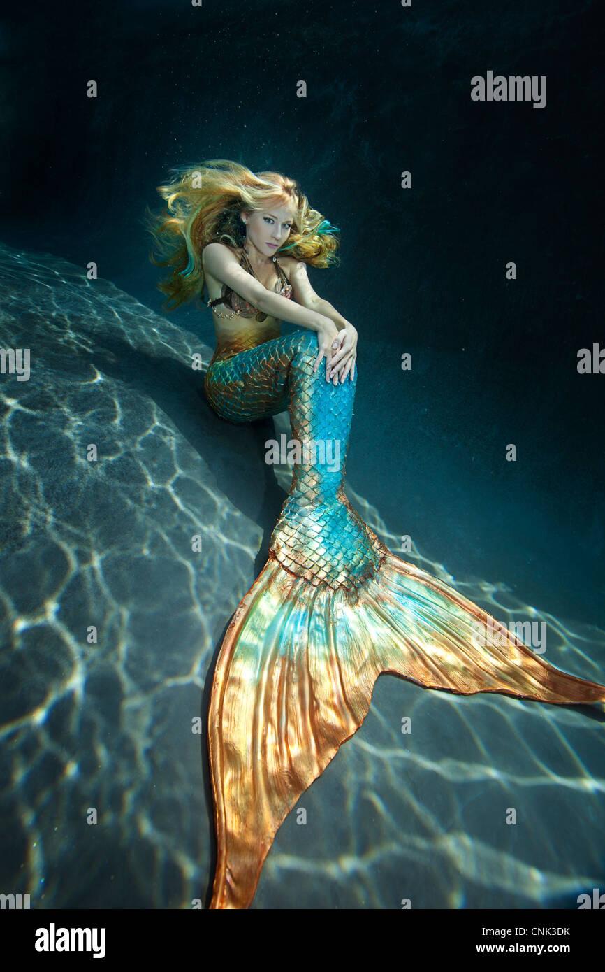Meerjungfrau sitzt auf dem Boden unter Wasser Stockbild