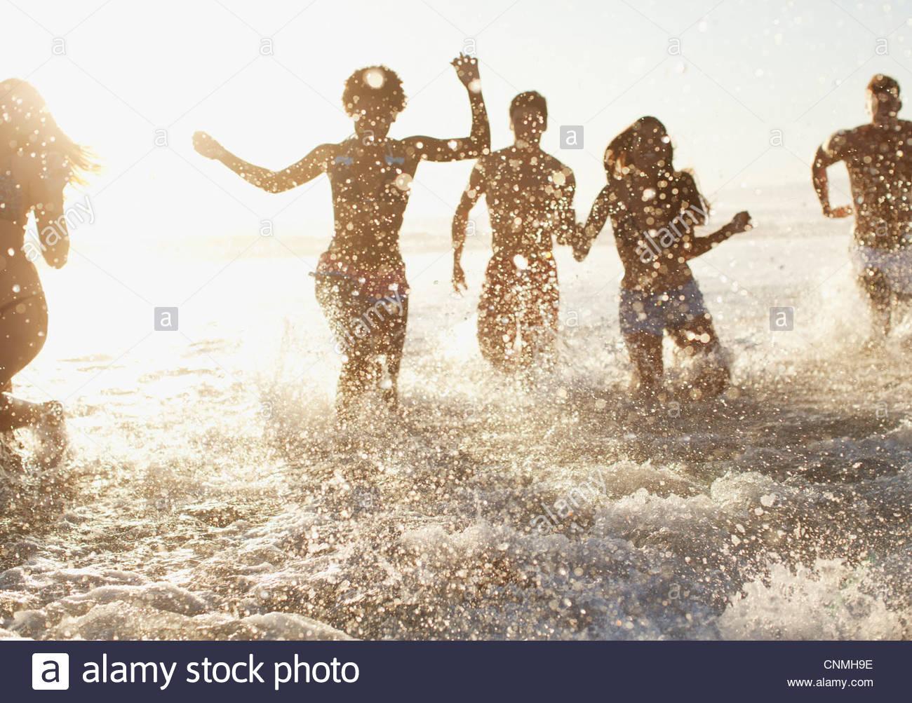 Freunde spielen in Wellen am Strand Stockfoto