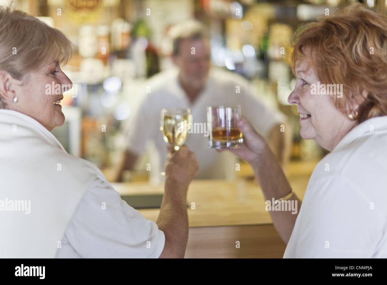 Ältere Frauen Toasten einander in Bar Stockbild
