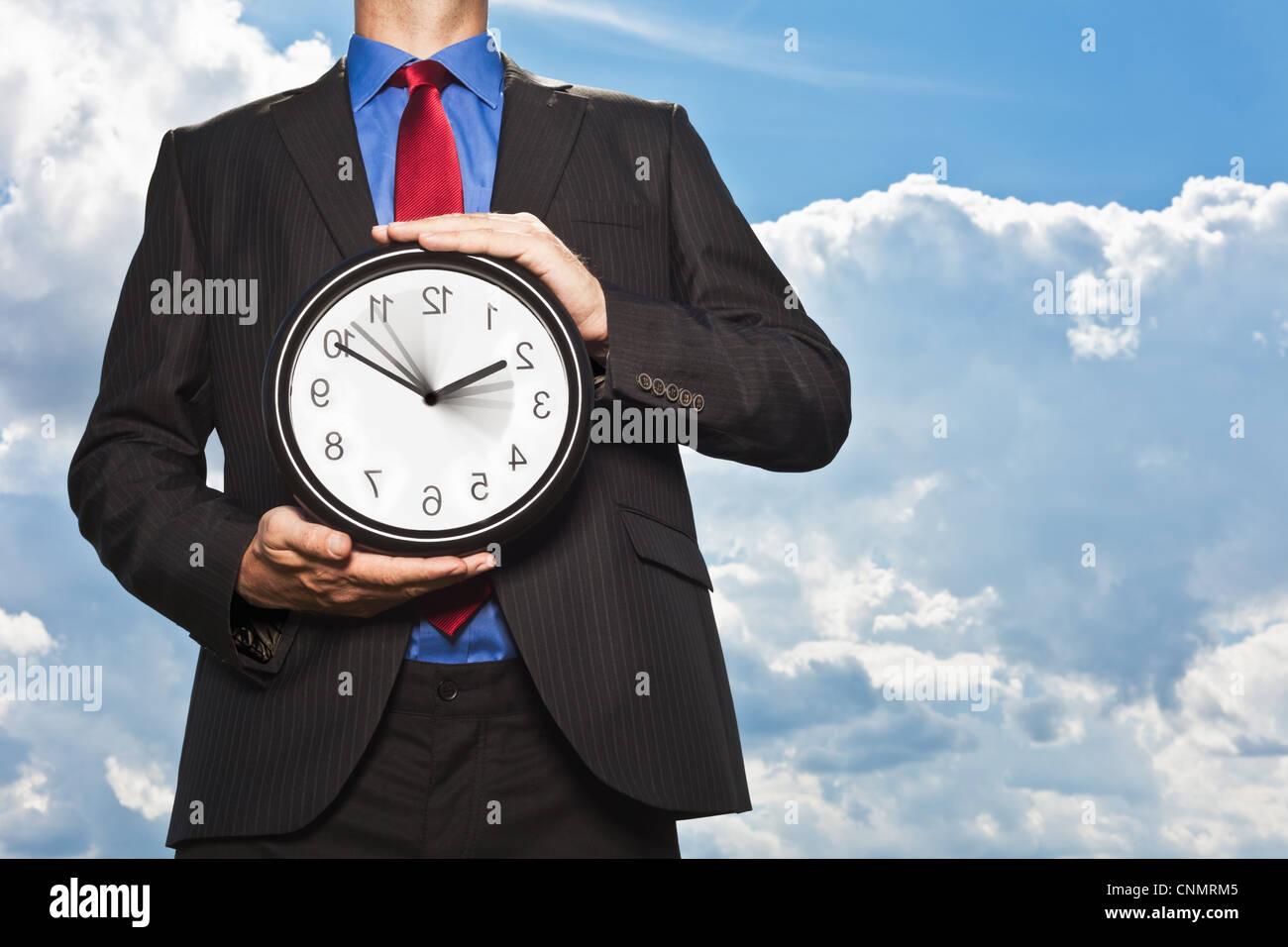 Geschäftsmann hält rückwärts Uhr Stockbild