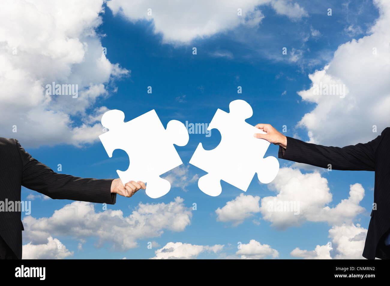 Geschäftsleute, die Puzzleteile halten Stockbild