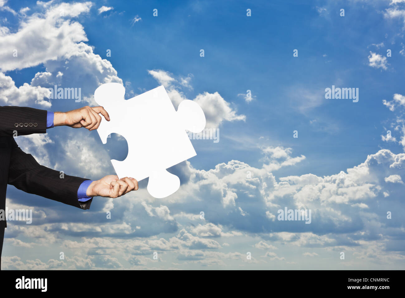 Geschäftsmann hält Puzzleteil Stockbild