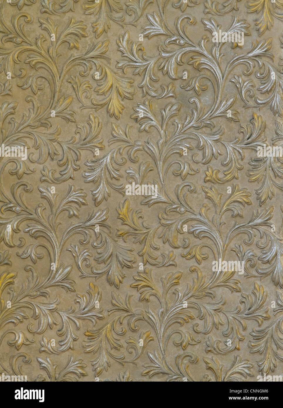 Fragment der Betonmauer mit der silbernen und goldenen Blättern Stockbild