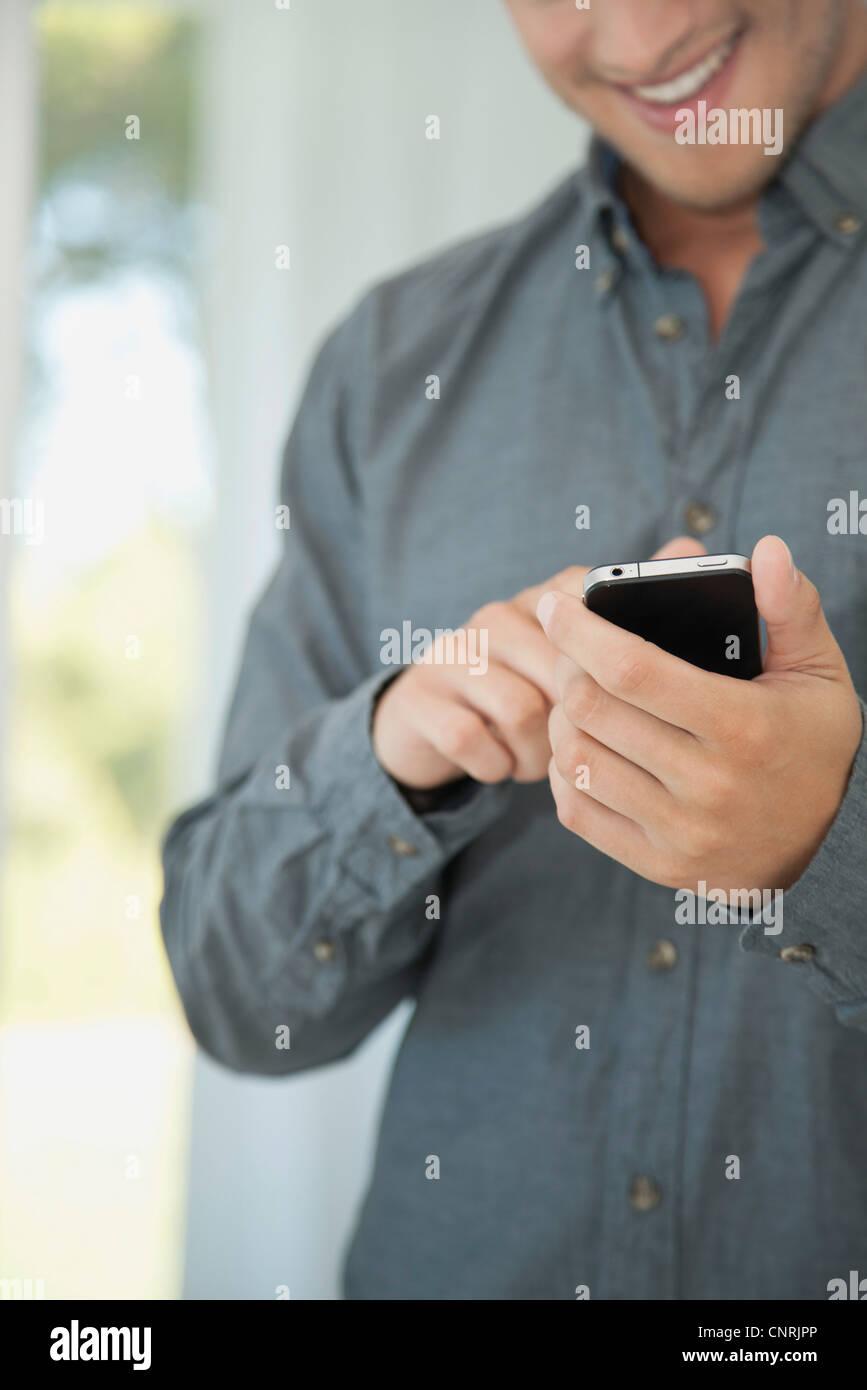Mann mit Smartphone, Mittelteil Stockbild