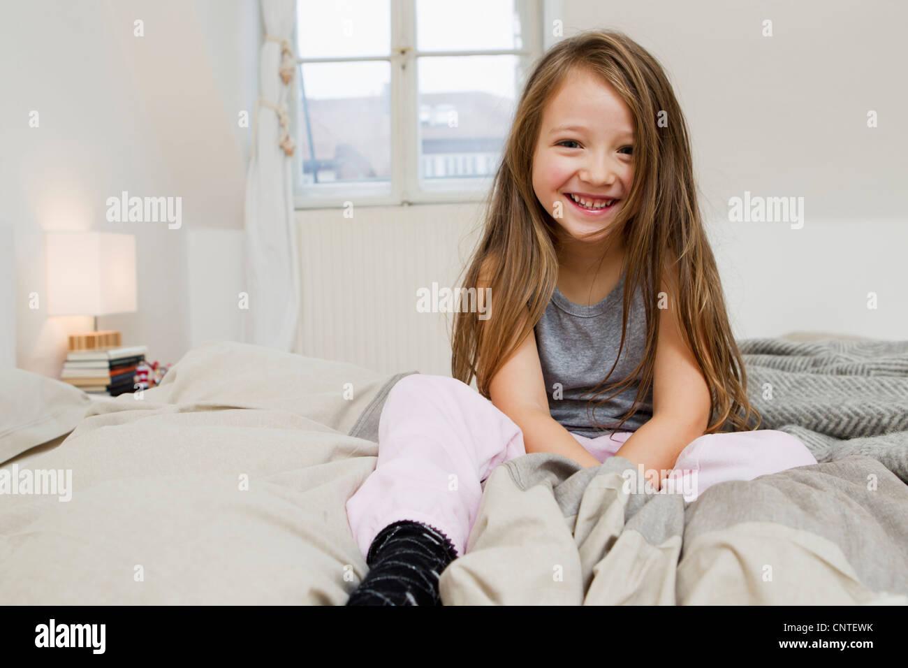 l chelndes m dchen sitzt auf bett stockfoto bild 47867055 alamy. Black Bedroom Furniture Sets. Home Design Ideas