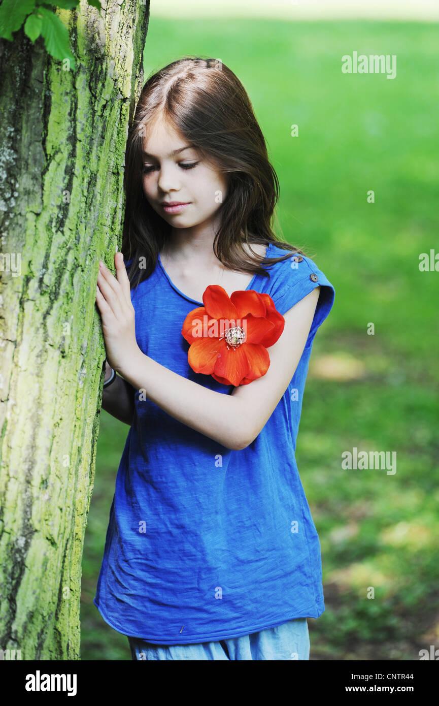Mädchen lehnte sich gegen Baum im park Stockfoto
