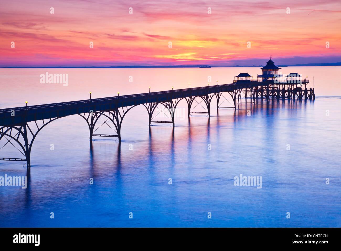 Die Sonne geht über den Bristolkanal hinter dem Pier in Clevedon, Somerset, England, UK Stockfoto