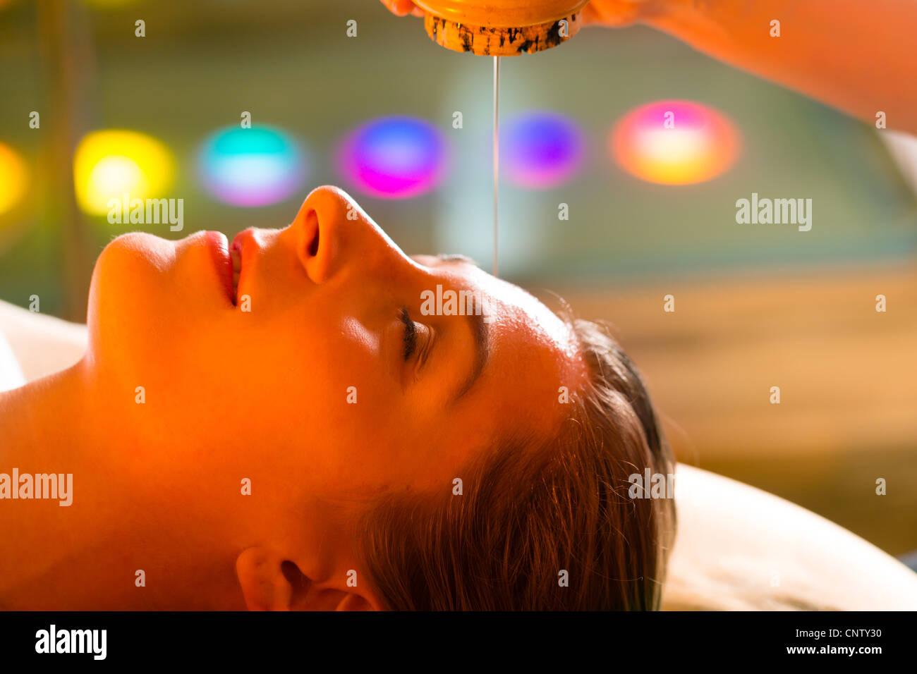 Frau genießen eine Ayurveda Öl massage-Behandlung in einem Spa mit Chromotherapie Stockbild