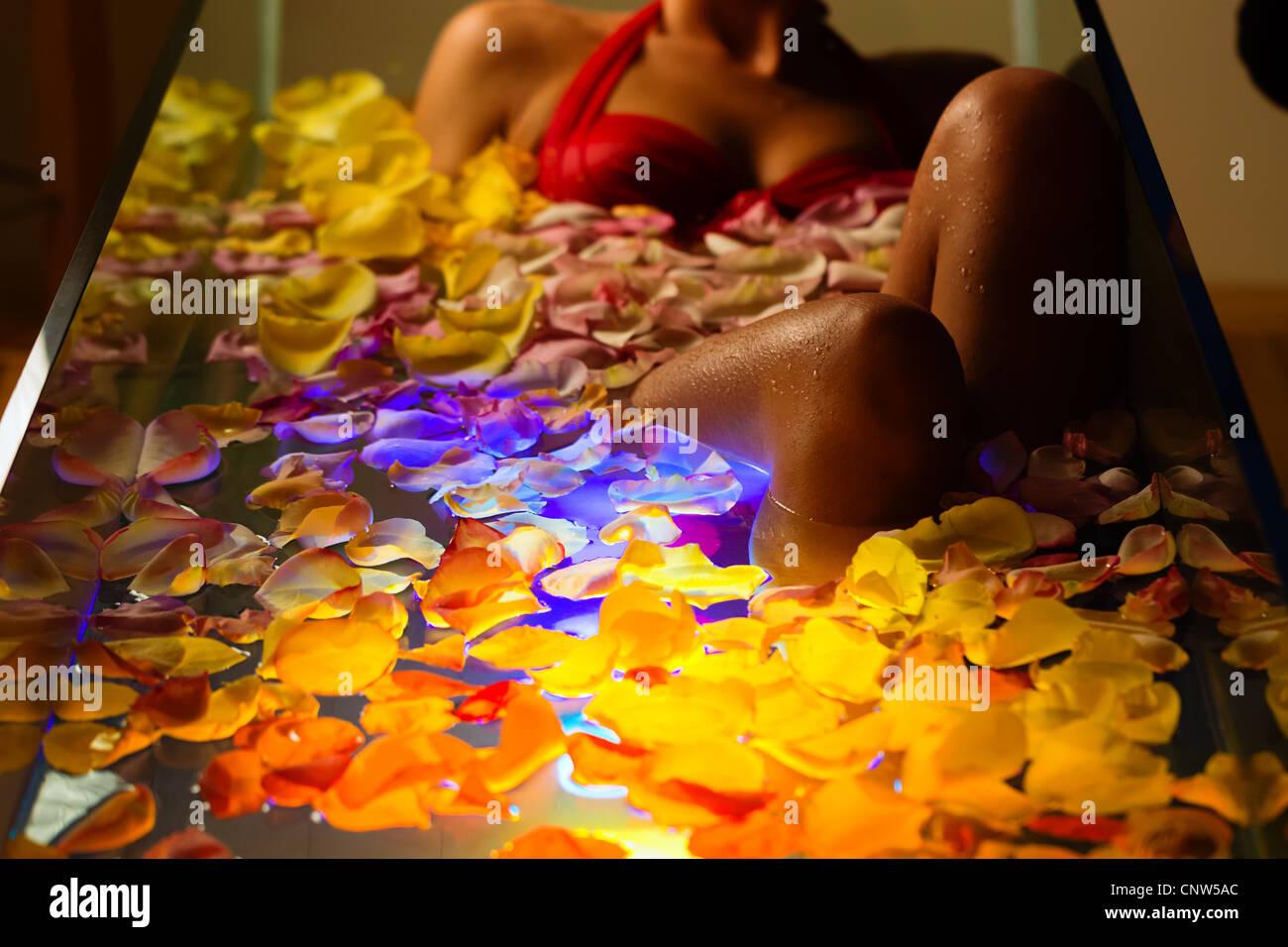 Frau Baden im Spa mit Farbtherapie, die Badewanne ist mit bunten Lichtern, vieler Blumenblüten auf Wanne beleuchtet. Stockbild