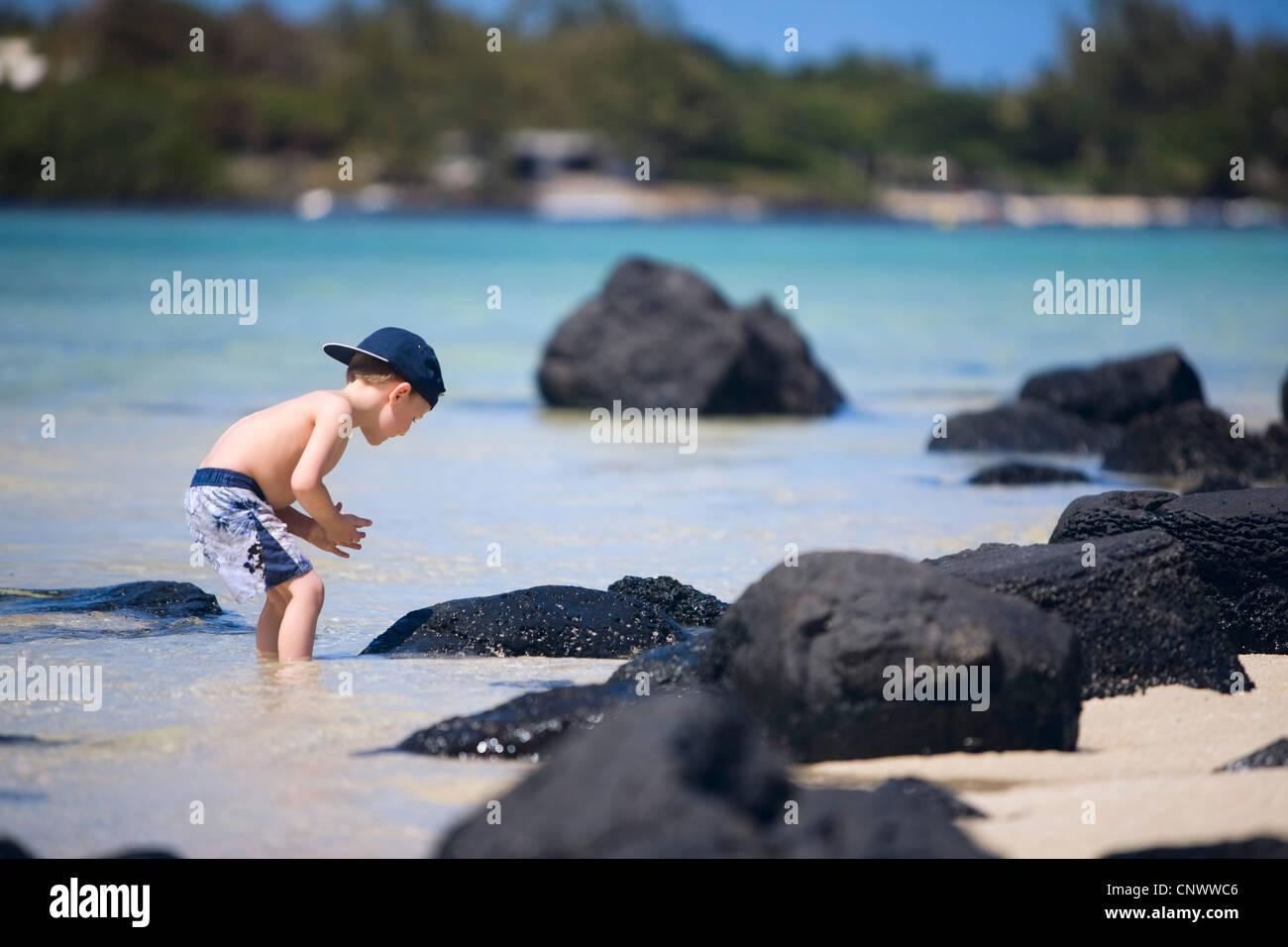 kleiner junge erkunden felsen am ocean beach f r krebse und fische mauritius indischer ozean. Black Bedroom Furniture Sets. Home Design Ideas