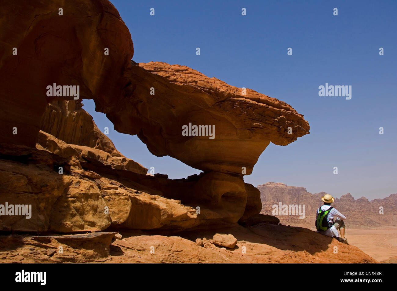 Touristen sitzen auf einem Felsvorsprung blickte auf ein Tal der Wüste Wadi Rum, Jordanien Stockbild