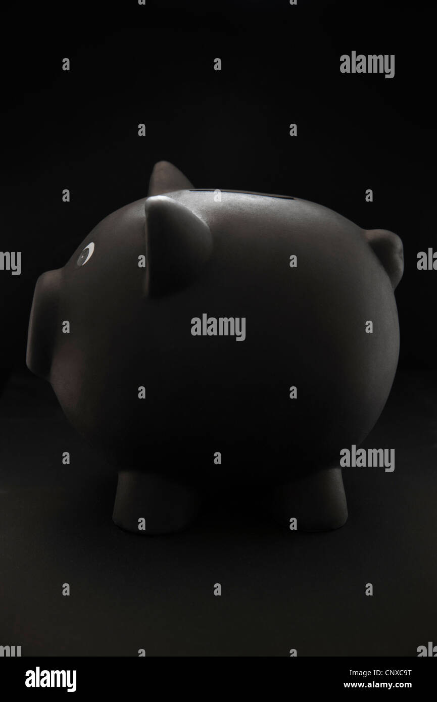 Profil von einem schwarzen Sparschwein auf schwarzem Hintergrund Stockbild