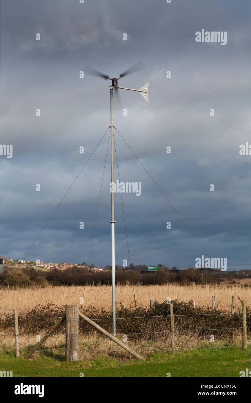 kleine ländliche Windkraftanlage gegen Gewitterhimmel bewölkt Bewölkt Stockbild