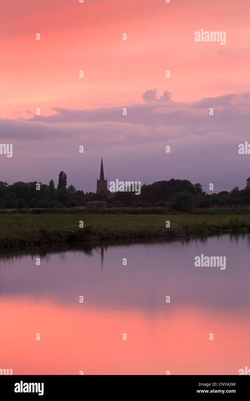 Sonnenuntergang über der Themse und der Kirche Spire von Lechlade, Cotswolds, Oxfordshire, England. Sommer Stockbild