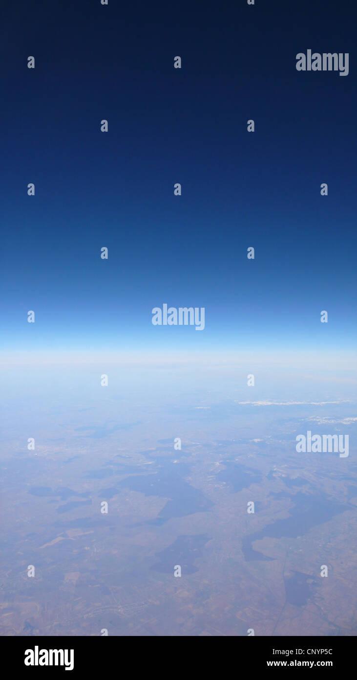 Blick aus dem Flugzeugfenster an einem wolkenlosen Himmel über einer weiten Landschaft Stockbild