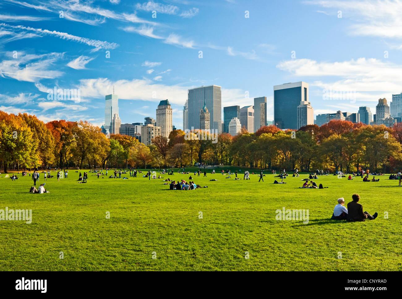 Menschen entspannen im Central Park in New York City, im Herbst, mit Blick auf die Skyline von Central Park South Stockbild