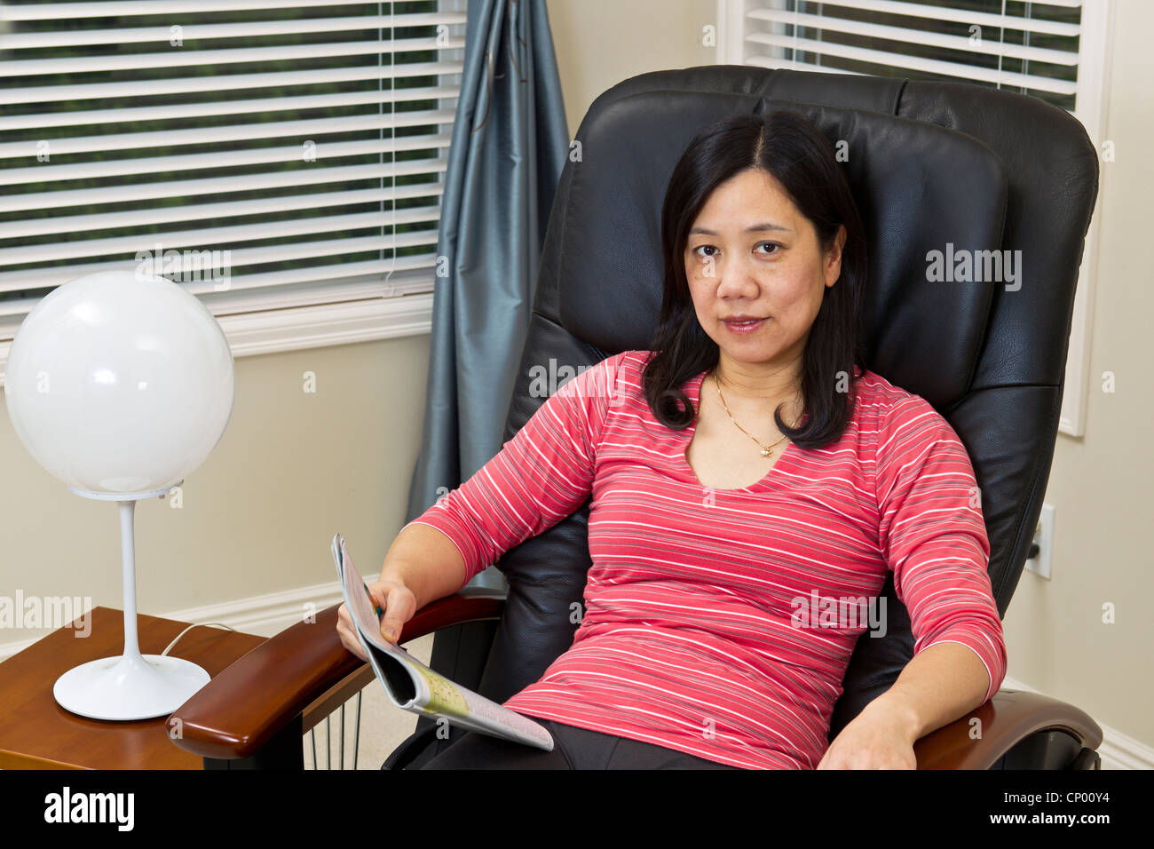 Asiatische Frau beim Entspannen in Massage Stuhl zu Hause
