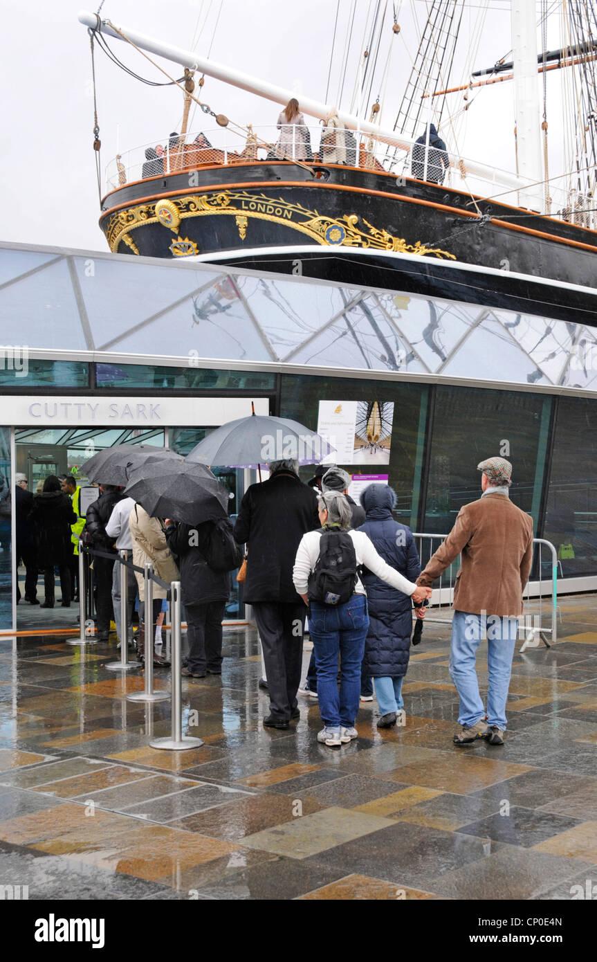 Cutty Sark Touristenattraktion mit Touristen Schlange im Regen unter Sonnenschirmen restauriert Stockbild
