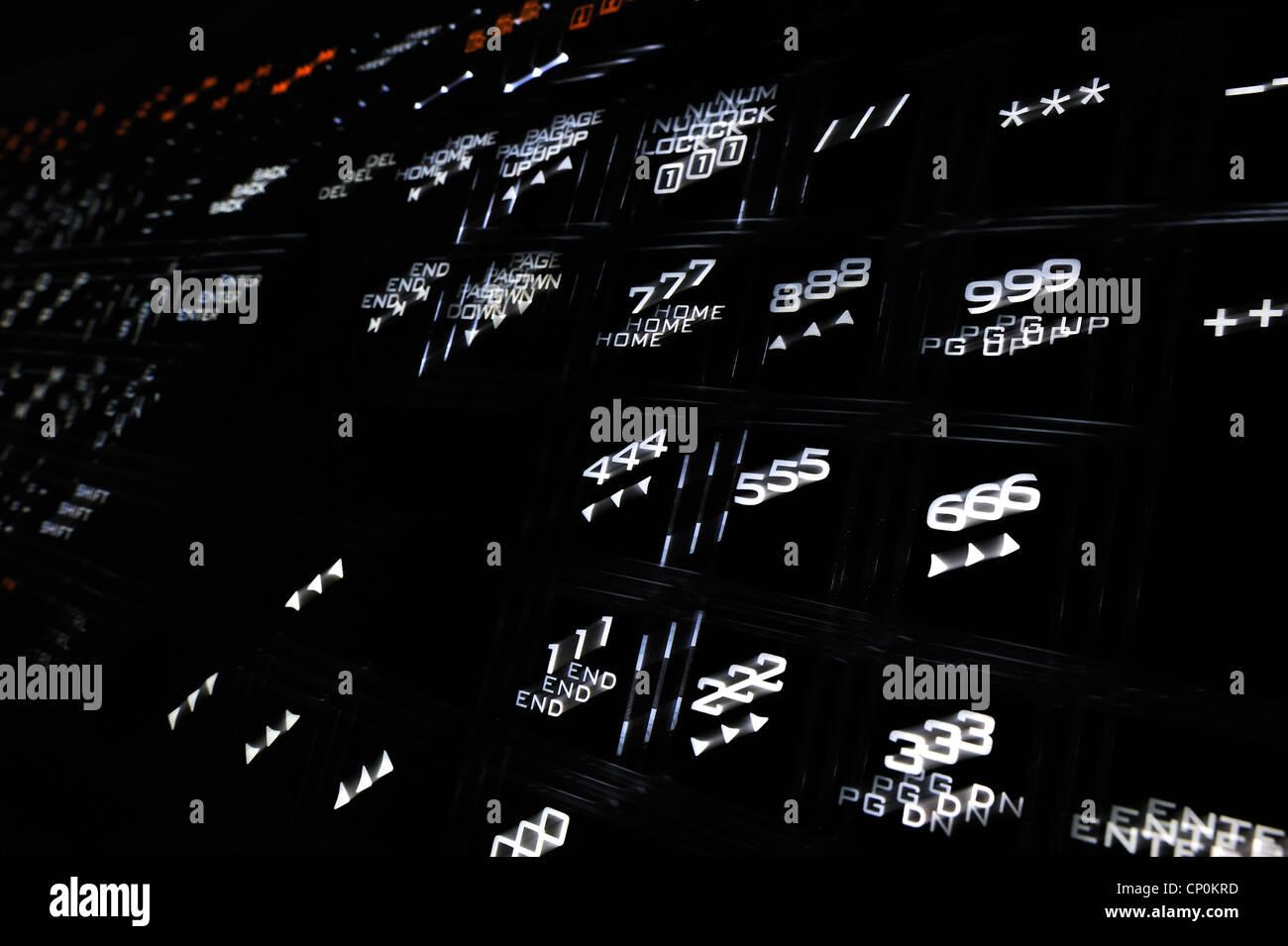 Schwarze Tastatur mit verschwommenen beleuchtet beleuchtete weiße Zahlen auf Tasten Stockbild