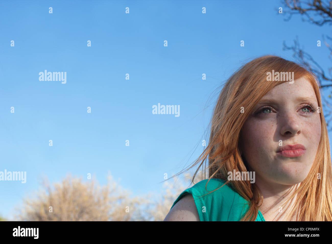 16 Jahre alten Mädchen sitzen im Freien eine Spiel beobachten. Stockbild