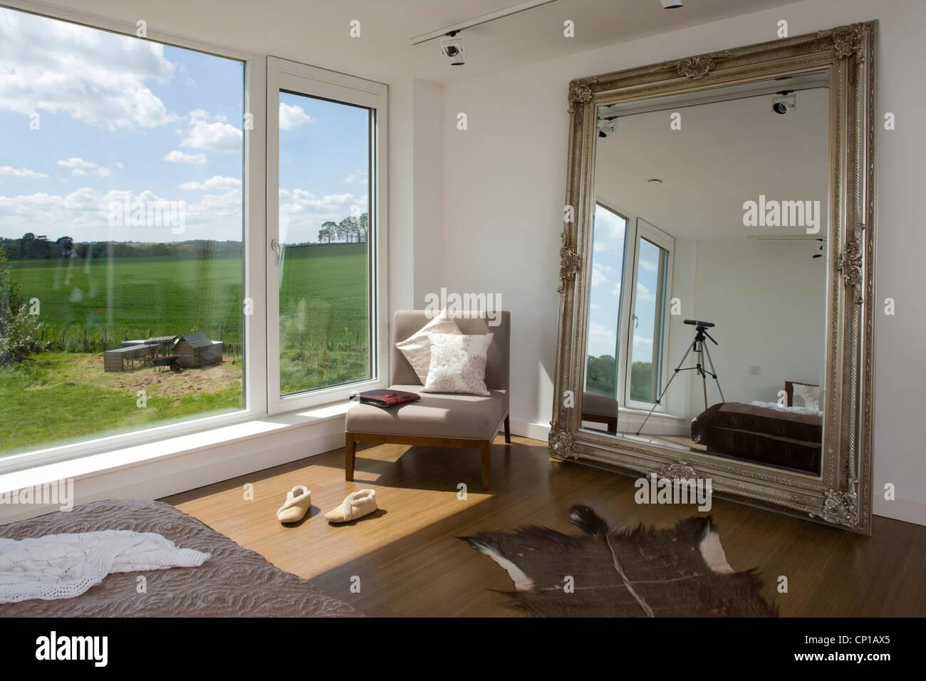 Stuhl am Fenster mit übergroßer Spiegel im Schlafzimmer des CO2 ...