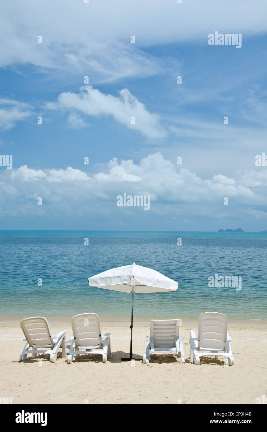 Liegestühle und Sonnenschirme am schönen tropischen Sandstrand ...