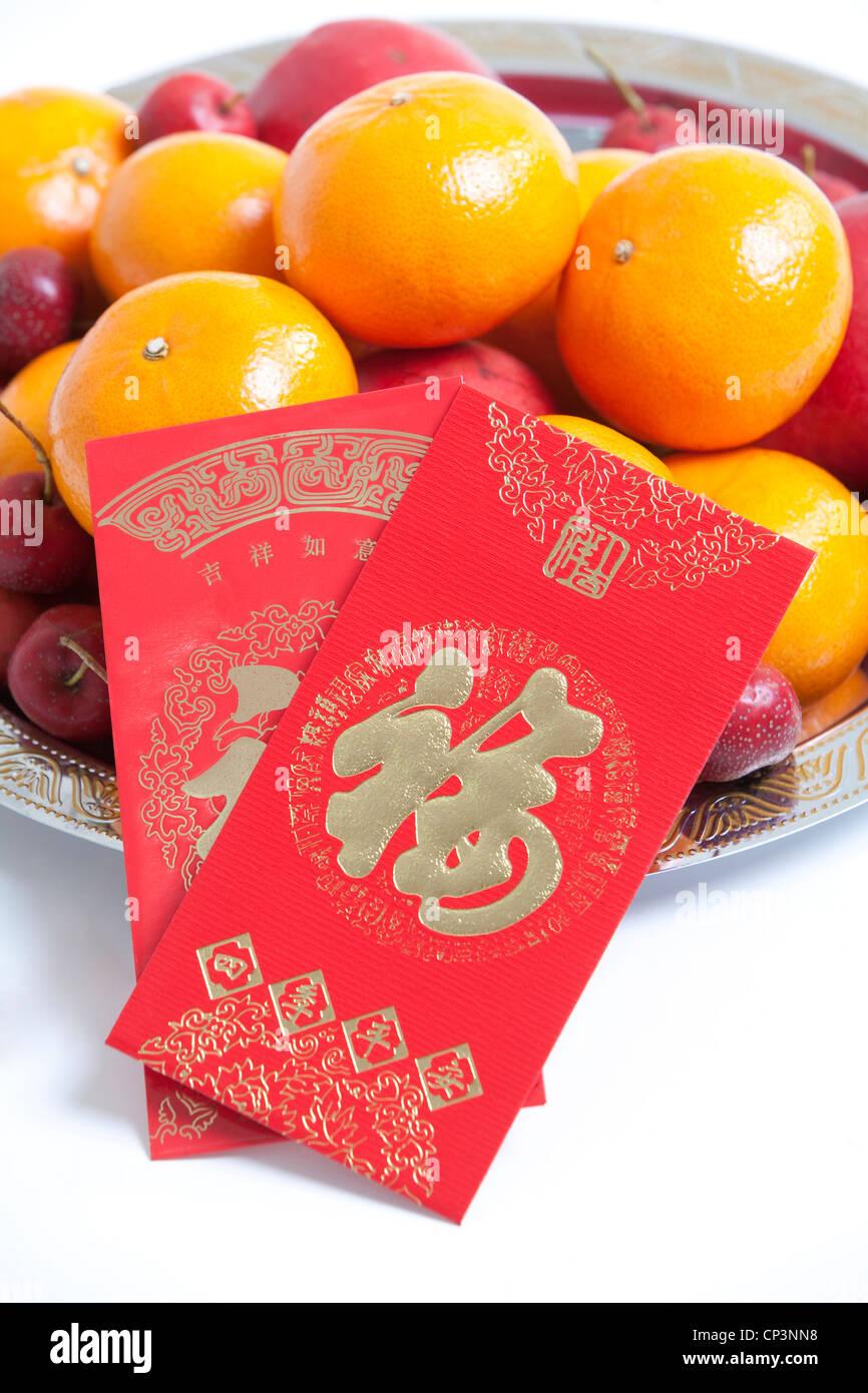 Rote Umschläge auf Obstschale zum chinesischen Neujahr feiern Stockbild