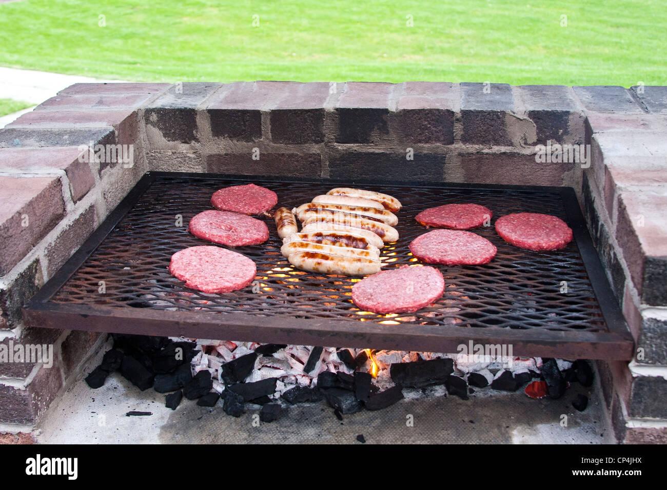 Beautiful Burger Und Würstchen Kochen Auf Einen Backstein Grill Stockbild