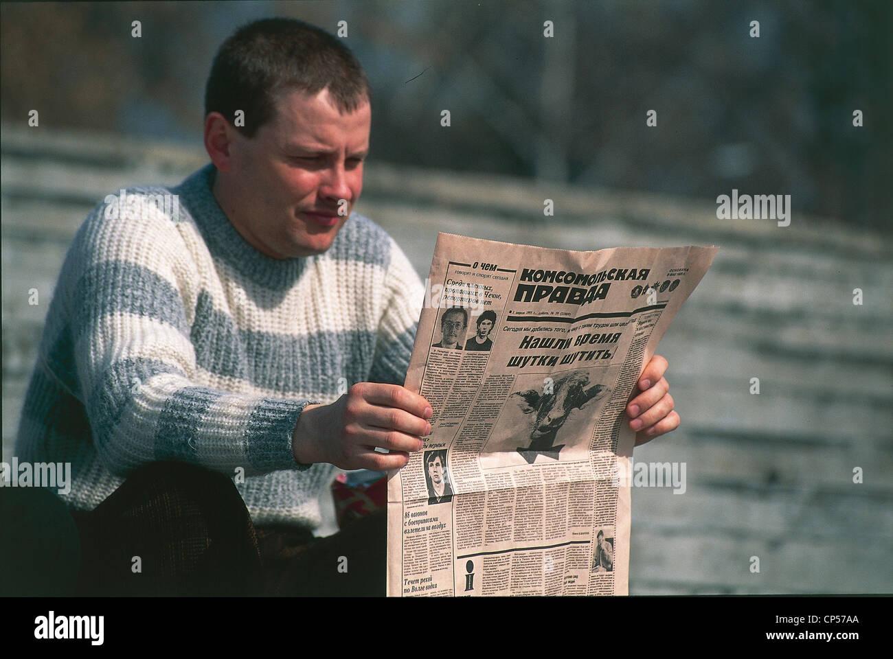 Russland-XX Jahrhundert. Neunziger Jahre - Sibirien - Irkutsk. Mann liest Zeitung Komsomolskaya Pravda Stockbild